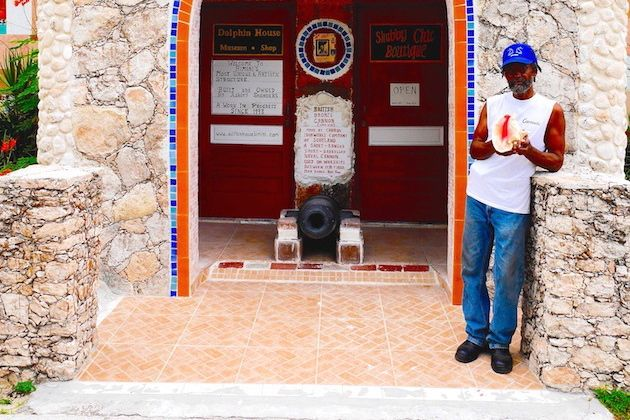 Bahamian artist Ashley Saunders outside his masterwork, Dolphin House in North Bimini | Credit: Zickie Allgrove