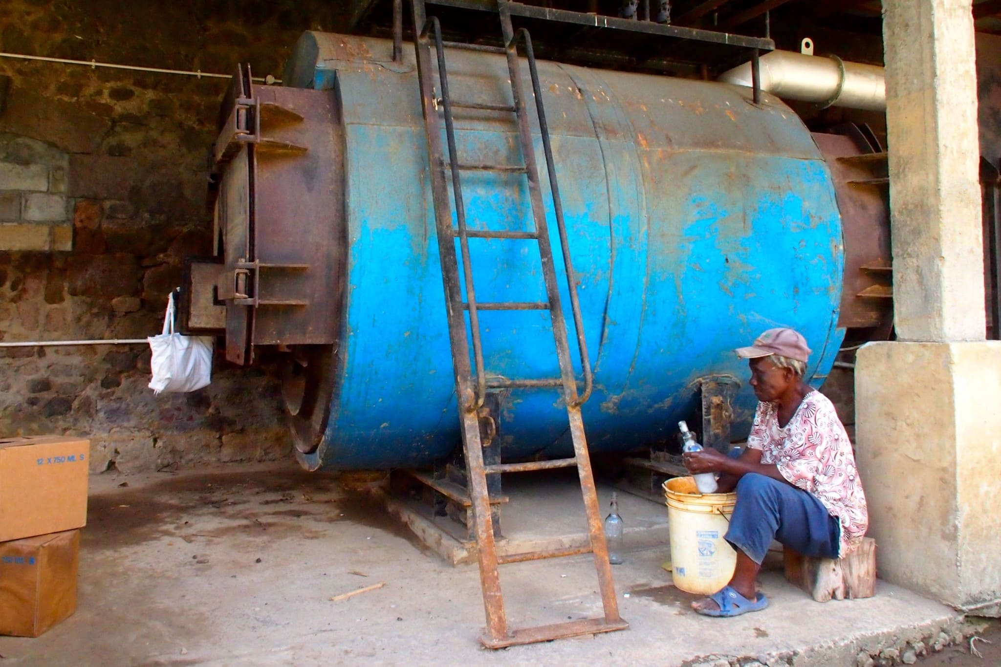Washing bottles by hand at the Macoucherie Distillery, Dominica | SBPR