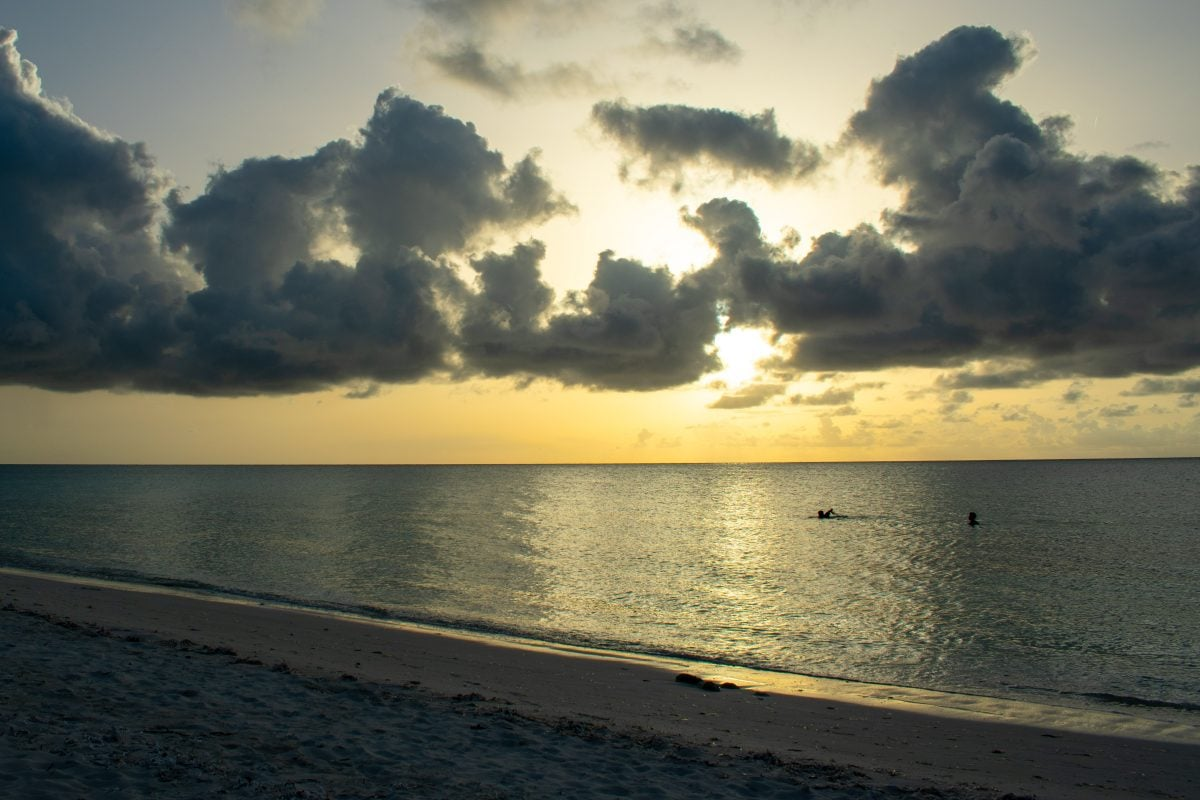 Swimming beneath the setting sun at Sandy Point Beach in North Caicos | SBPR