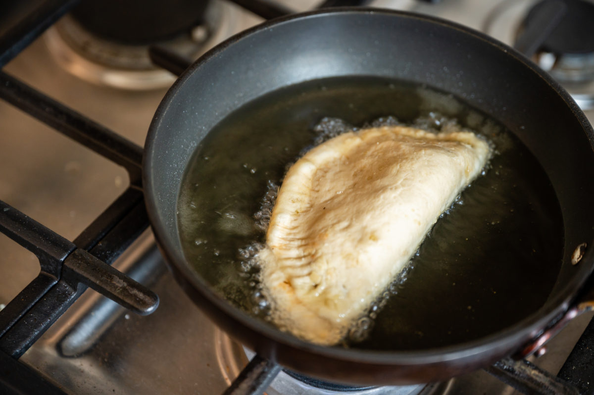 Saltfish pate frying to a golden brown